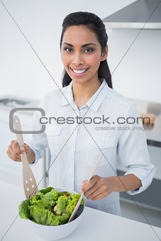 Attractive black haired woman preparing salad in kitchen