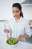 Lovely peaceful woman preparing salad in kitchen
