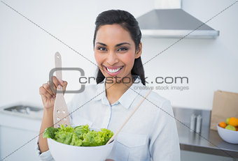 Beautiful smiling woman showing salad smiling at camera