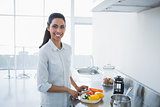 Cute smiling woman preparing salad standing in bright kitchen