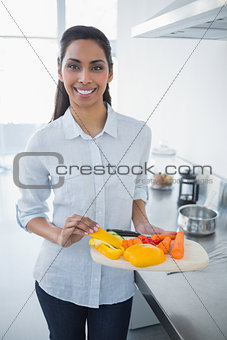 Beautiful proud woman showing vegetables smiling at camera