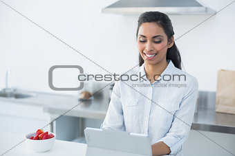 Beautiful woman working on her tablet standing in her kitchen