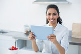 Lovely young woman holding her tablet standing in bright kitchen
