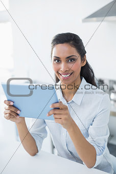 Attractive peaceful woman holding her tablet smiling cheerfully at camera