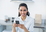 Natural smiling woman holding her smartphone looking at camera