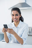 Cute calm woman holding her smartphone while smiling at camera