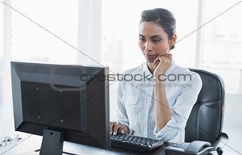 Beautiful concentrated businesswoman sitting at her desk