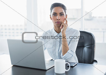 Attractive thoughtful businesswoman sitting at her desk