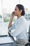 Beautiful calm woman phoning with her smartphone sitting at her desk