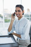 Pretty businesswoman phoning with smartphone smiling at camera