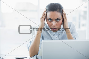 Beautiful stern businesswoman sitting at her desk while suffering from headache
