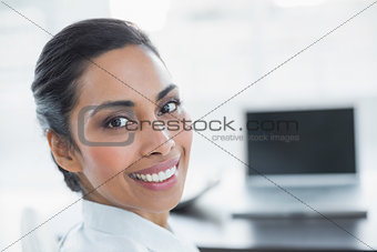 Beautiful smiling businesswoman sitting in bright office