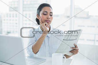 Focused businesswoman reading newspaper sitting at her desk