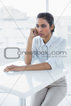 Beautiful calm businesswoman sitting thoughtful at desk