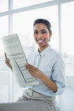 Gleeful chic businesswoman holding newspaper smiling at camera