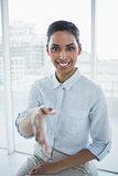 Friendly chic businesswoman reaching her hand