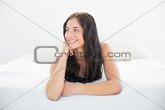 Happy woman looking away in bed