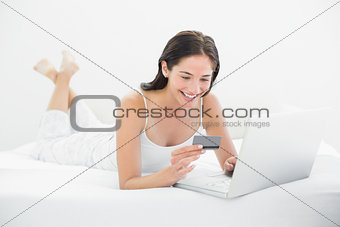 Casual woman doing online shopping in bed
