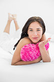 Woman with heart shaped pillow blowing kiss in bed