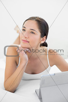 Thoughtful woman with tablet PC in bed