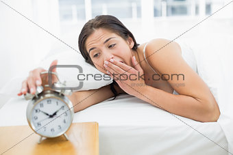 Woman yawning while extanding hand to alarm clock
