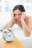 Woman looking at alarm clock while lying in bed