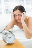 Serious woman with alarm clock lying in bed