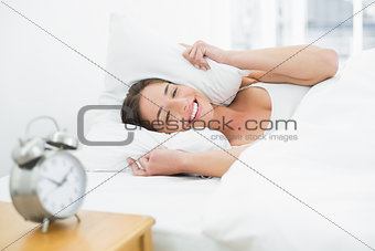 Smiling woman covering ears with pillow and alarm clock on side table