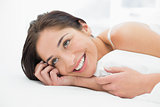 Happy young woman resting in bed