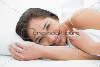 Close up of a pretty smiling woman resting in bed