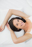 Smiling young woman resting in bed