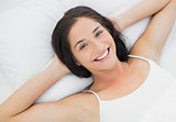 Pretty smiling young woman resting in bed