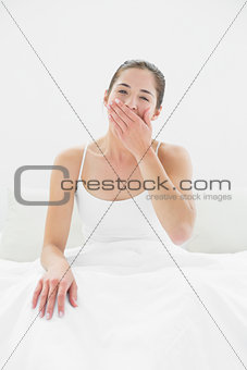 Portrait of a woman yawning in bed