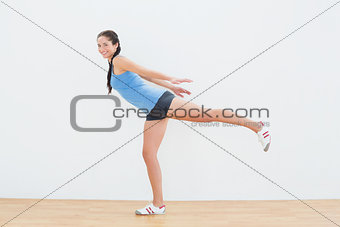 Woman standing on one leg in fitness center