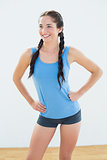 Smiling woman in sportswear and plaits looking away