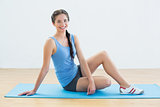 Full length of a smiling woman sitting on exercise mat