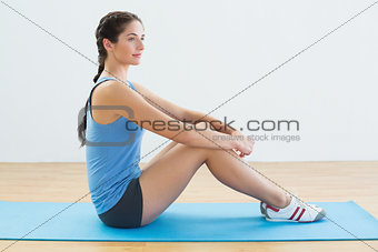 Profile shot of a fit woman sitting upright on exercise mat