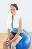 Woman with towel around neck sitting on exercise ball