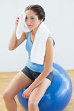 Tired woman with towel around neck on exercise ball