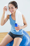 Smiling woman with towel around neck sitting on exercise ball