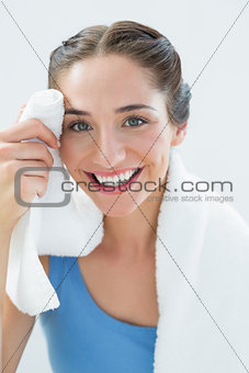 Close up of a smiling woman wiping sweat with towel