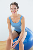 Smiling fit woman sitting on exercise ball