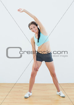 Full length portrait of a smiling woman stretching hand