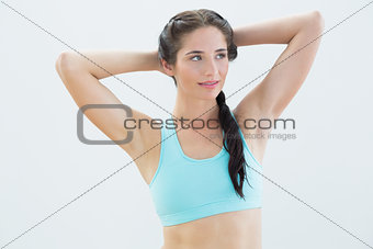 Fit young woman standing with hands behind head