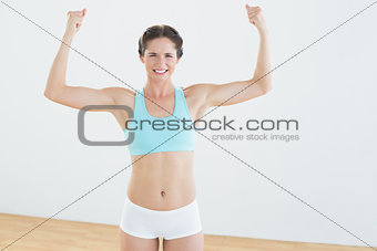 Fit woman in sportswear standing with clenched fists