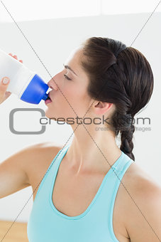 Close up of a fit woman drinking water at the gym