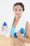 Woman with dumbbells and water bottle at fitness studio