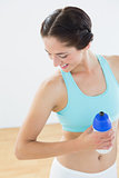 Fit smiling woman holding water bottle at fitness studio