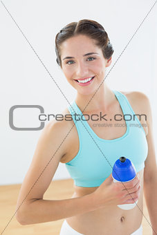 Fit smiling young woman holding water bottle at fitness studio