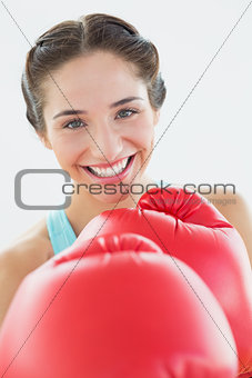 Close up of a beautiful smiling woman in red boxing gloves